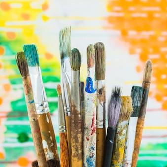 Grupo de pincéis em fundo colorido