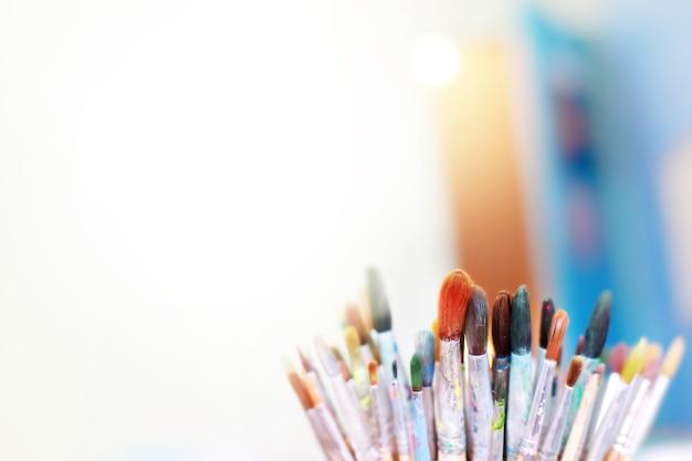 Grupo de pincéis usados com fundo limpo, foco suave e profundidade de composição de campo e cor vintage.