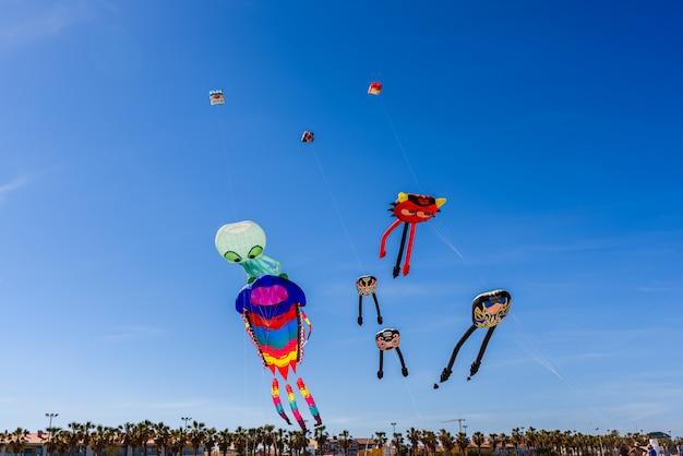 Grupo de pipas com formas de animais voando durante um festival de verão
