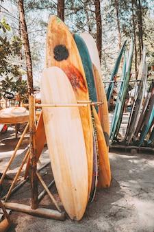Grupo de placas de ressaca coloridas diferentes em uma pilha disponível para o aluguel na praia. pranchas de surf verticais, efeito do tom da cor do vintage.
