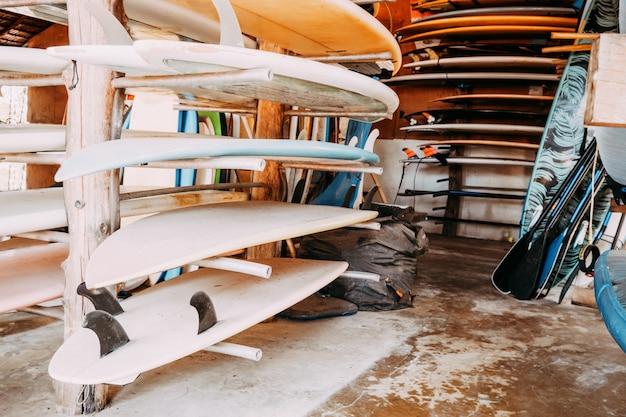 Grupo de placas de ressaca coloridas diferentes em uma pilha disponível para o aluguel na praia.