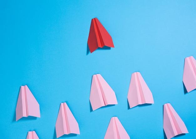 Grupo de planos de papel rosa segue o primeiro vermelho contra uma superfície azul. o conceito de unir uma equipe para atingir objetivos, um líder forte, um grupo altamente eficaz