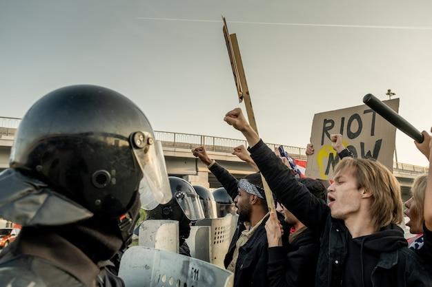 Grupo de policiais com capacetes segurando escudos antimotim enquanto ataca rebeldes com cartazes ao ar livre