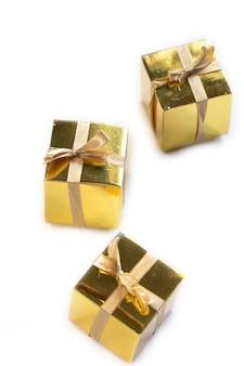 Grupo de presente espumante ouro ou caixas de presente em uma fileira com laço isolado