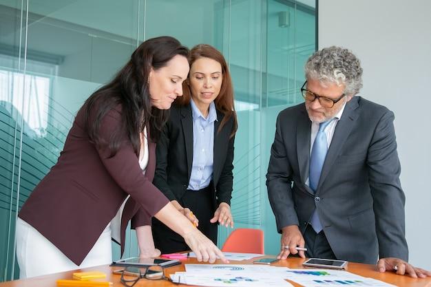 Grupo de profissionais analisando relatórios em papel com tabelas e gráficos