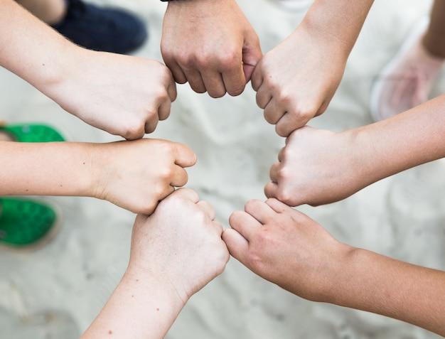 Grupo de protesto pacífico e unidade de manifestante e parceria de diversidade como mãos em um punho de diversas pessoas conectadas entre si