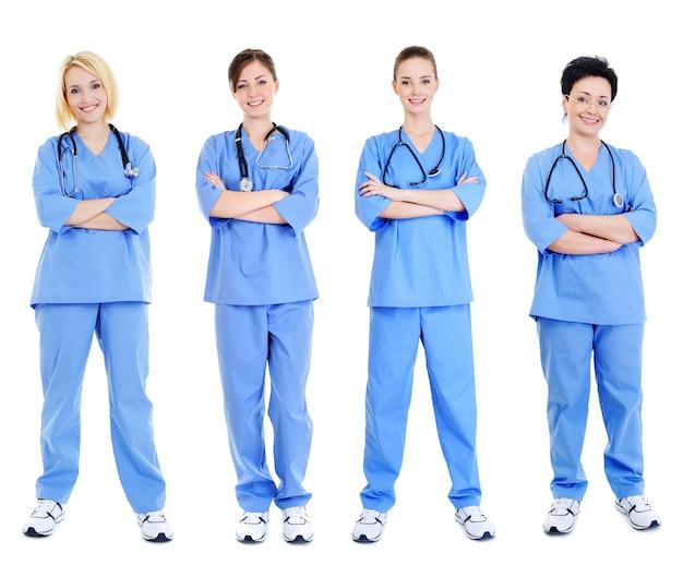 Grupo de quatro alegres médicas em uniformes azuis isolados no branco