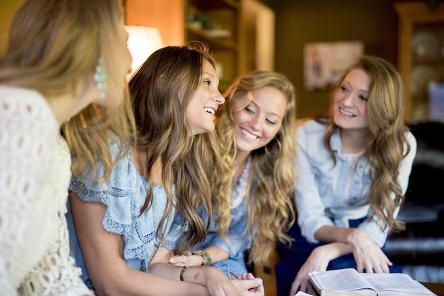 Grupo de quatro amigas rindo em casa enquanto lêem