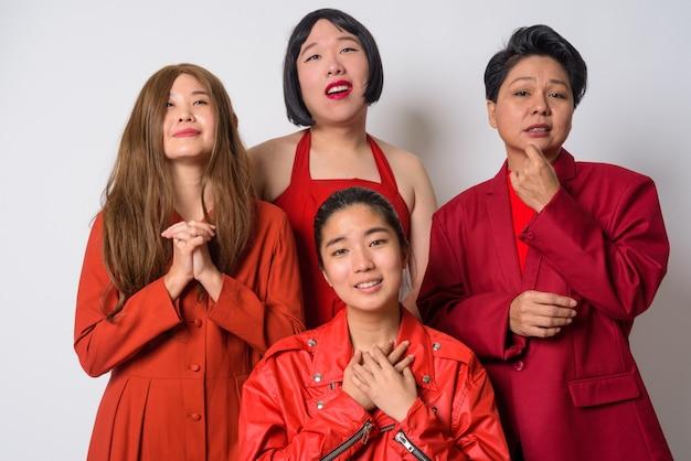 Grupo de quatro amigos asiáticos com diversidade de idade e personalidades juntos contra uma parede branca
