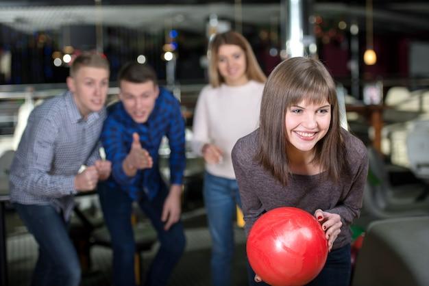 Grupo de quatro amigos em uma pista de bowling que tem o divertimento.