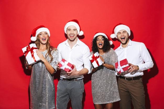 Grupo de quatro amigos felizes e bem vestidos, isolados sobre o espaço vermelho, comemorando