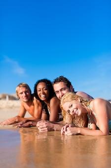 Grupo de quatro amigos - homens e mulheres - na praia com muita diversão em suas férias