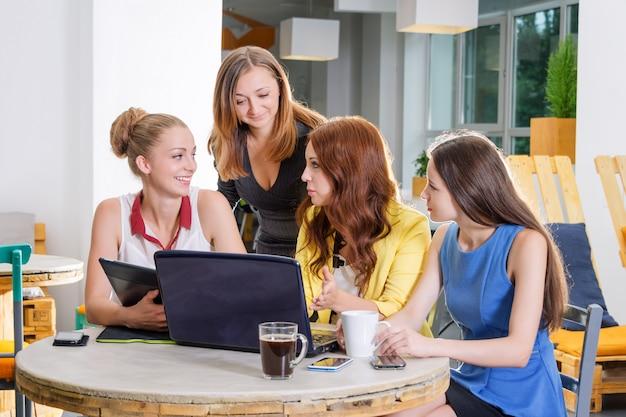 Grupo de quatro empresária bonita trabalhando togeather com novo projeto de inicialização usando o computador portátil em loft moderno