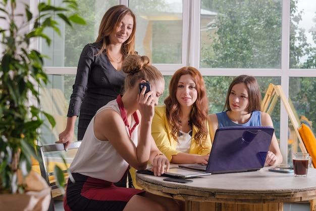Grupo de quatro empresária bonita trabalhando togeather com novo projeto de inicialização usando o computador portátil em loft moderno Foto Premium
