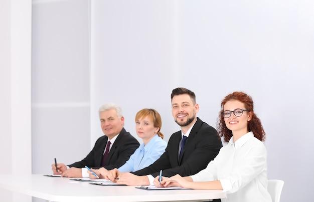 Grupo de quatro executivos em ternos elegantes sentados à mesa de trabalho em um auditório iluminado