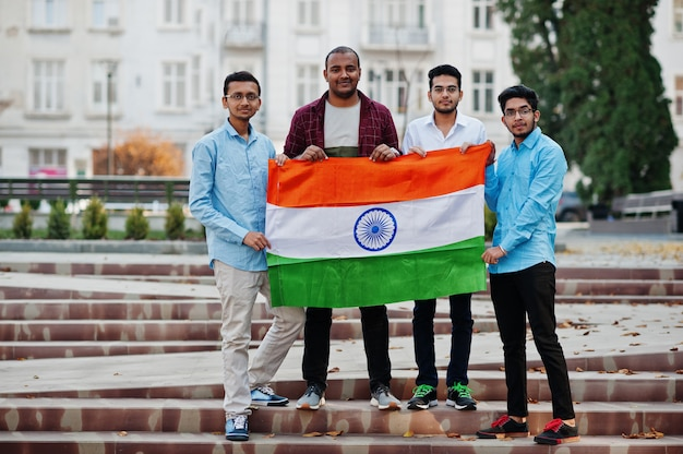 Grupo de quatro homens indianos do sul asiático com bandeira da índia.