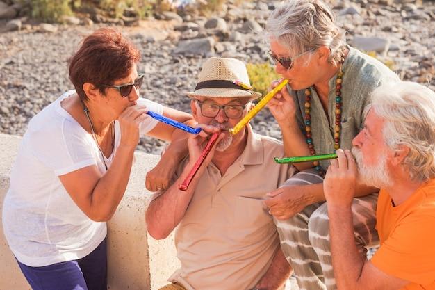 Grupo de quatro idosos e pessoas se divertindo juntos e comemorando algo - adultos maduros curtindo o estilo de vida