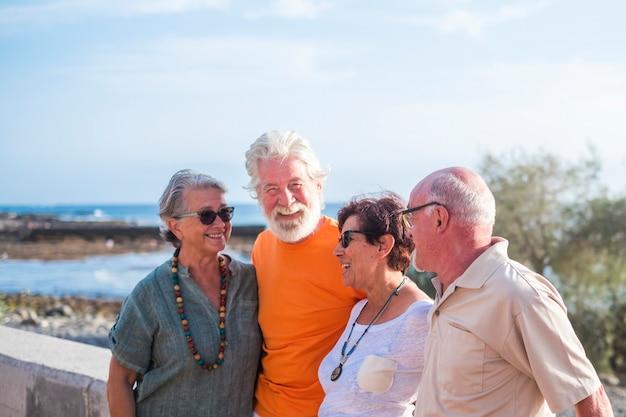 Grupo de quatro idosos felizes e pessoas maduras conversando e se divertindo juntos na praia com o mar ao fundo - conceito de amizade e relacionamento