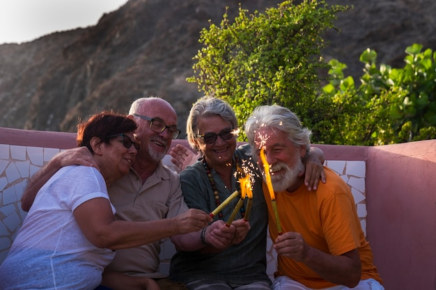 Grupo de quatro idosos juntos no parque, sentados no banco brincando com algo com fogo - pessoas maduras felizes no ano novo ou comemorando algo ou uma festa
