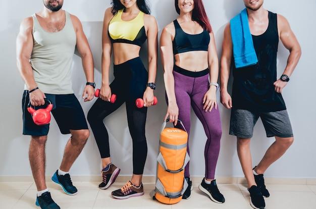 Grupo de quatro jovens amigos atléticos juntos no ginásio na parede cinza após uma sessão de treino difícil