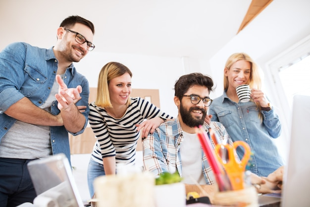 Grupo de quatro jovens empresários bem-sucedidos satisfeitos, olhando para o oduct final em um laptop no escritório, juntamente com prazer.