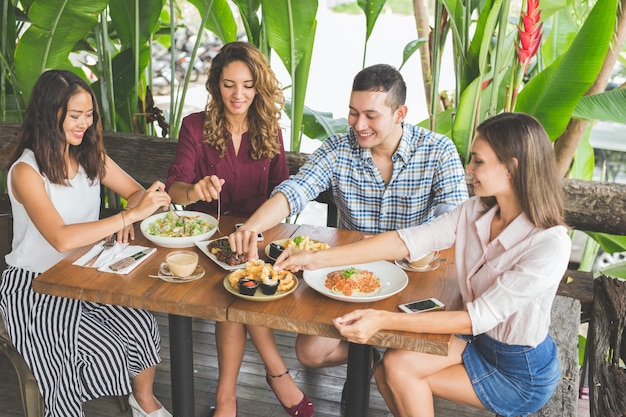 Grupo de quatro melhores amigos almoçando juntos em um café