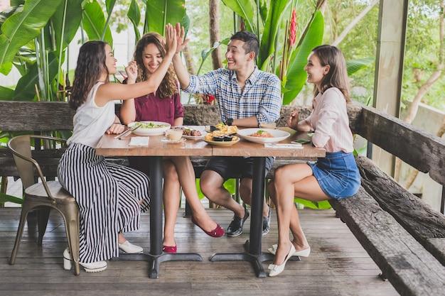 Grupo de quatro melhores amigos se divertindo enquanto almoçam juntos em um café