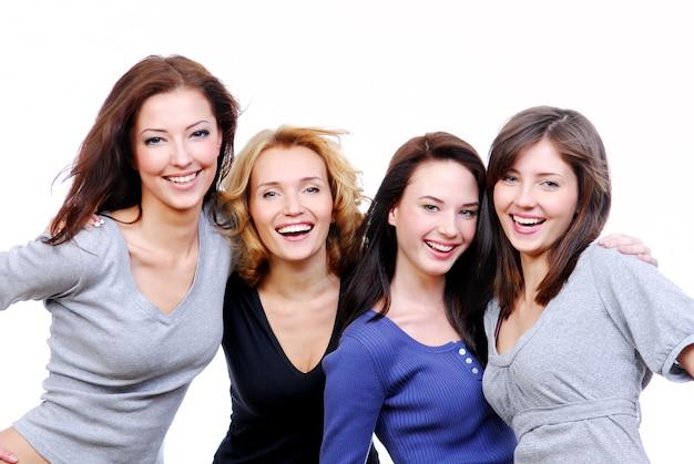 Grupo de quatro mulheres jovens bonitas e sexy e felizes. isolado no branco