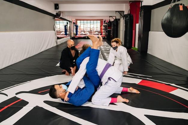 Grupo de quatro parceiros de artes marciais e um instrutor praticando novas técnicas com máscaras devido ao cobiçado 19 em um tapete de ginástica