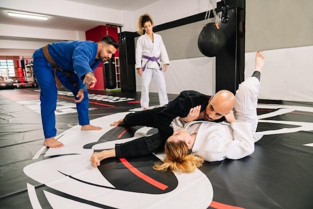 Grupo de quatro parceiros de judô de artes marciais e um instrutor praticando novas técnicas em um tapete de ginástica