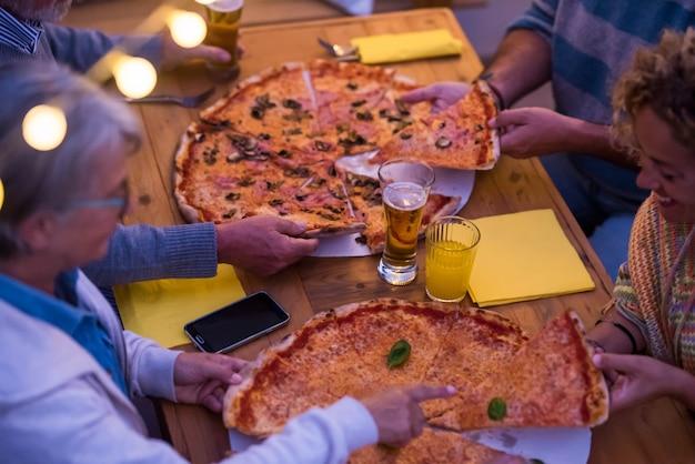 Grupo de quatro pessoas comendo pizza e bebendo cerveja juntas à noite em casa ou em um restaurante - família reunida comemorando algo