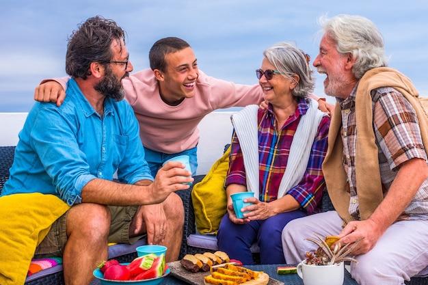 Grupo de quatro pessoas de todas as idades juntas em casa na varanda rindo e se divertindo e comendo alimentos como frutas e biscoitos - adolescente se divertindo com idosos e homem de meia-idade