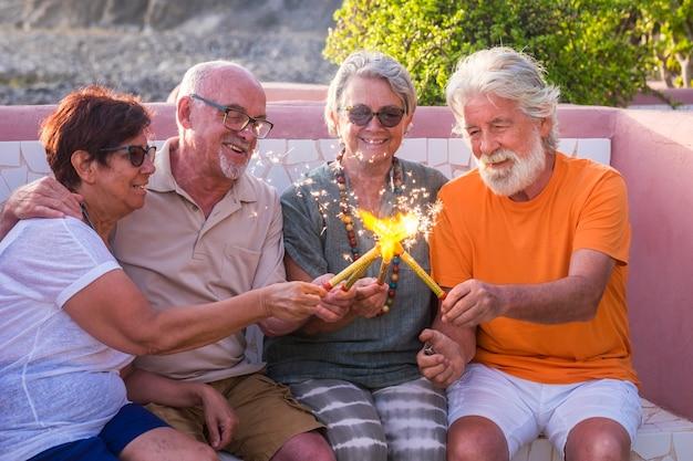 Grupo de quatro pessoas e idosos sentados em um banco juntos brincando e celebrando algo com fogo ou faíscas - festa ou ano novo