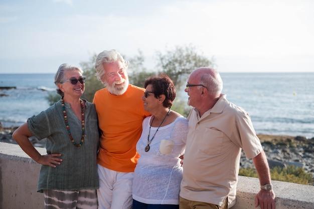 Grupo de quatro pessoas maduras se divertindo e conversando na praia - aposentados idosos sorrindo e rindo com o mar ao fundo