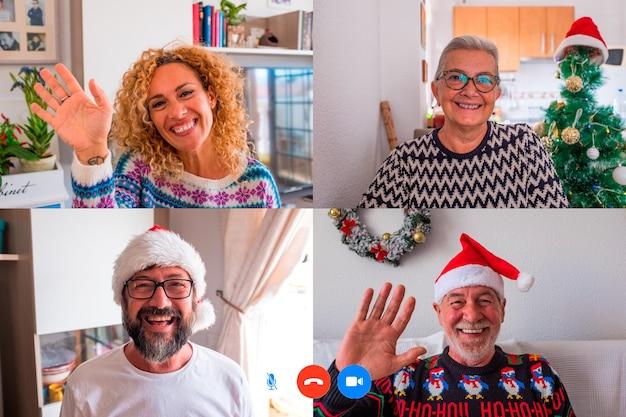 Grupo de quatro pessoas se divertindo, conversando em uma videochamada ou videoconferência no dia de natal, comemorando em bloqueio ou quarentena - família feliz usando tecnologia