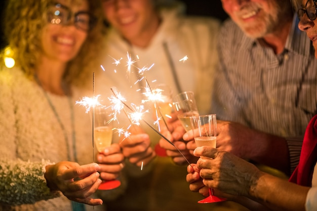 Grupo de quatro pessoas se divertindo e segurando taças de champanhe e espumantes comemorando o feliz ano novo juntos