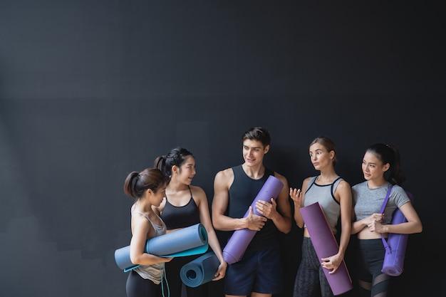 Grupo de raça mista de atletas caucasianos e asiáticos, mulheres e homens na parede preta, esperando para desfrutar da aula de ioga juntos