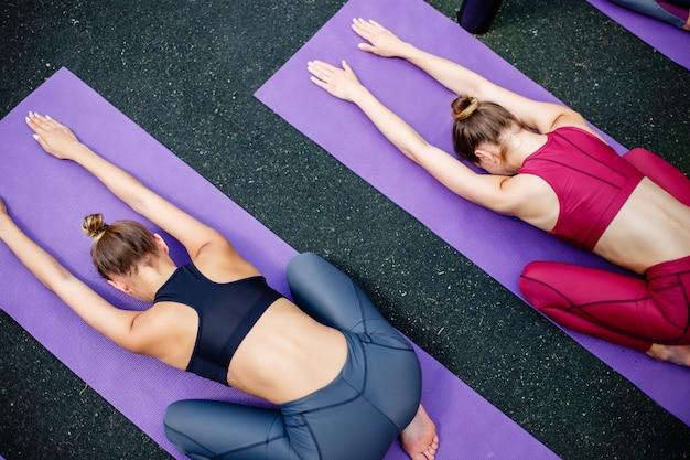 Grupo de raparigas que fazem a ioga ao ar livre, vista superior.