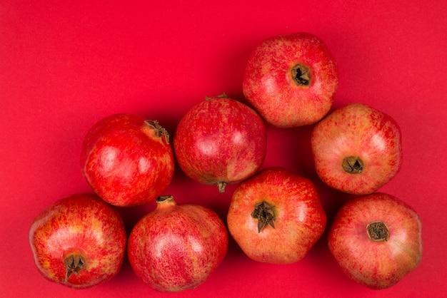 Grupo de romã doce sobre fundo vermelho.
