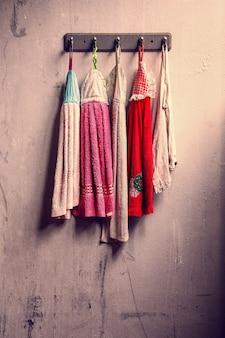 Grupo de roupas coloridas empoeiradas secando na parede de concreto do grunge