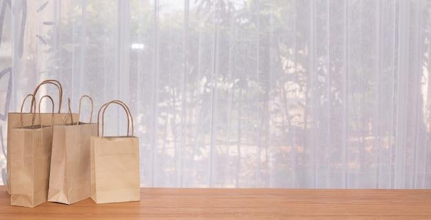 Grupo de sacos de papel kraft com cópia espaço na mesa de madeira com janelas de cortina branca.