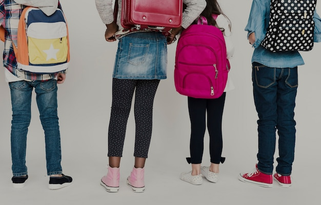 Grupo, de, schoolers, crianças, com, mochila, atrás de, vista traseira, branco, blackground