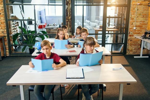 Grupo de seis jovens alunos felizes sentar à mesa e ler livros educacionais na lição.