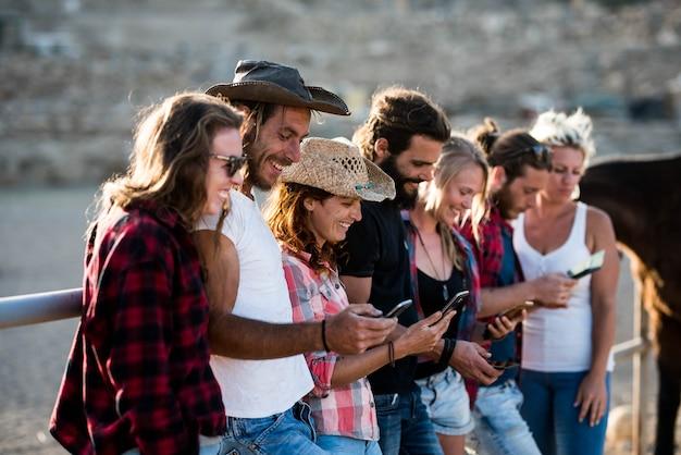 Grupo de sete pessoas usando seus fonees juntos, sorrindo e se divertindo em um rancho com cavalos ao fundo - grupo de adultos caucasianos curtindo com a tecnologia