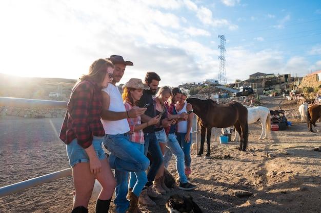 Grupo de sete pessoas usando seus telefones juntas em um rancho com cavalos ao fundo - pessoas online e redes sociais ou rede
