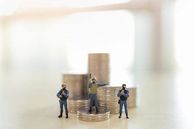 Grupo de soldado com arma de pessoas em miniatura na pilha de moedas