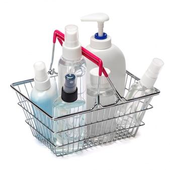 Grupo de spray de desinfetante para as mãos e frascos de sabonete líquido no pequeno carrinho de compras na mesa branca