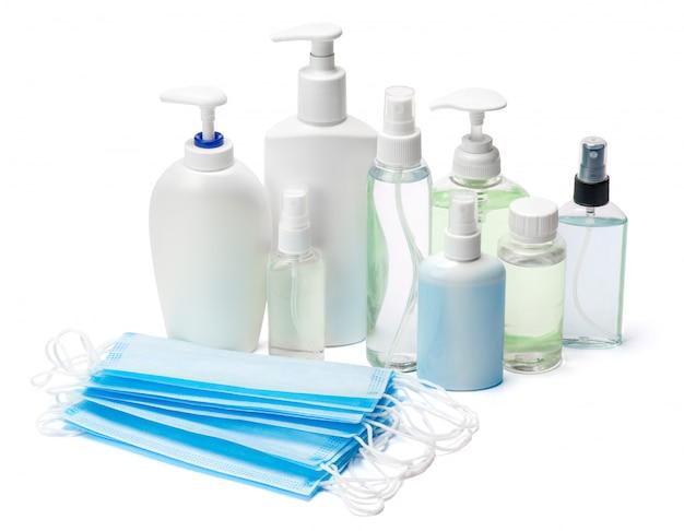Grupo de spray de desinfetante para as mãos e garrafas de sabonete líquido e máscaras protetoras na mesa branca
