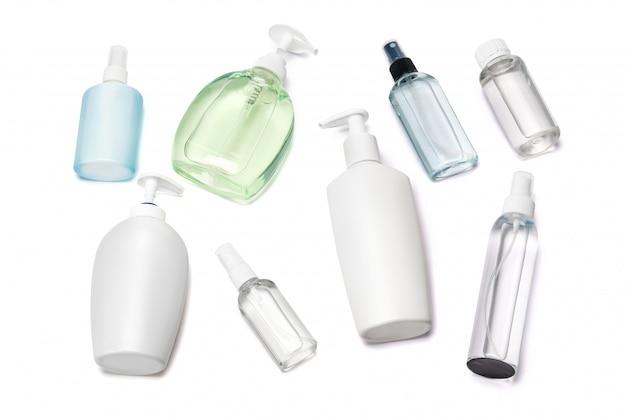 Grupo de spray desinfetante para as mãos e garrafas de sabonete líquido na mesa branca