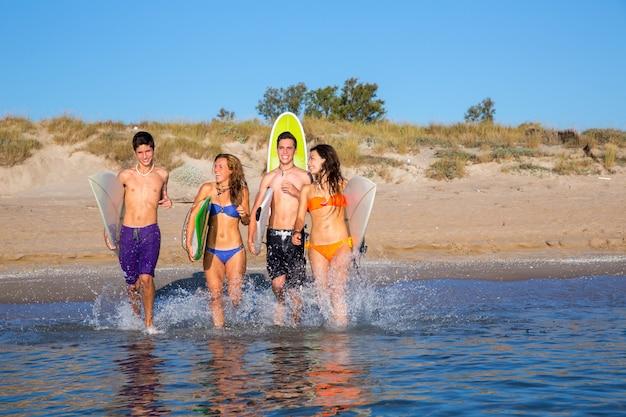 Grupo de surfistas adolescente correndo praia espirrando